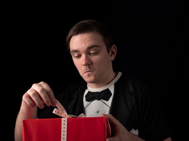 Junger mann in einem schwarzen t-shirt anzug öffnet ein rotes geschenk mit überraschung auf einem schwarzen