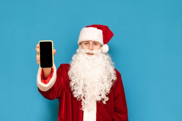 Junger mann in einem weihnachtsmannkostüm steht auf einem blauen, zeigt ein smartphone mit einem schwarzen bildschirm