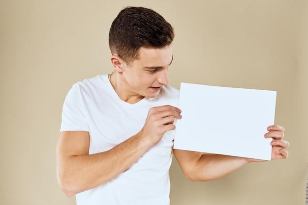Junger mann in einem weißen t-shirt, das leeres papierblatt hält