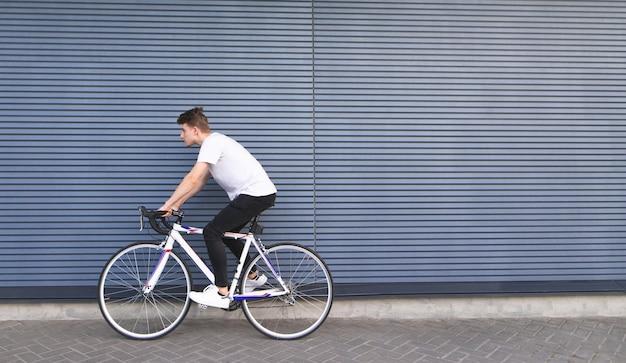 Junger mann in einem weißen t-shirt reitet auf einer weißen autobahn auf dem hintergrund der wand