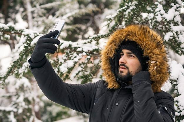 Junger mann in einem wintermantel, der selfie nimmt