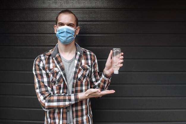 Junger mann in einer medizinischen maske, die flasche mit einem flüssigen antibakteriellen desinfektionsmittel hält