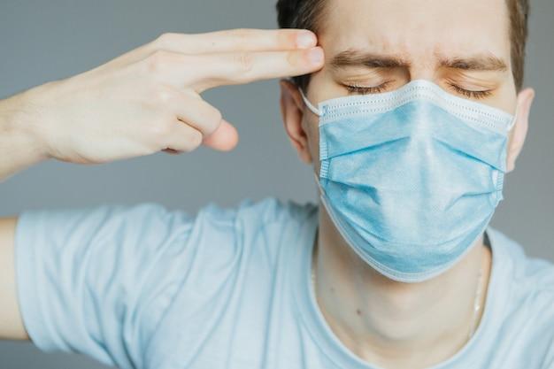 Junger mann in einer medizinischen maske zu hause hält seine finger eine waffe an seiner schläfe. töte, stress