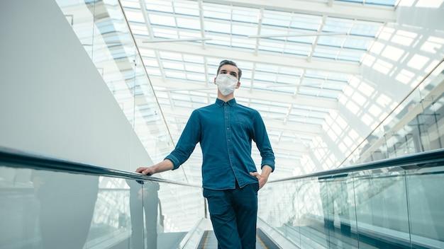 Junger mann in einer schutzmaske, die auf den rolltreppenstufen steht.