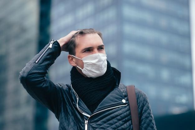 Junger mann in einer schutzmaske, die auf der straße steht.