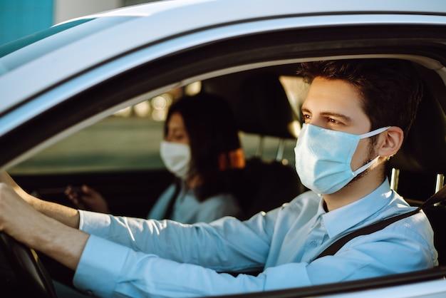 Junger mann in einer schutzmaske, die im auto sitzt