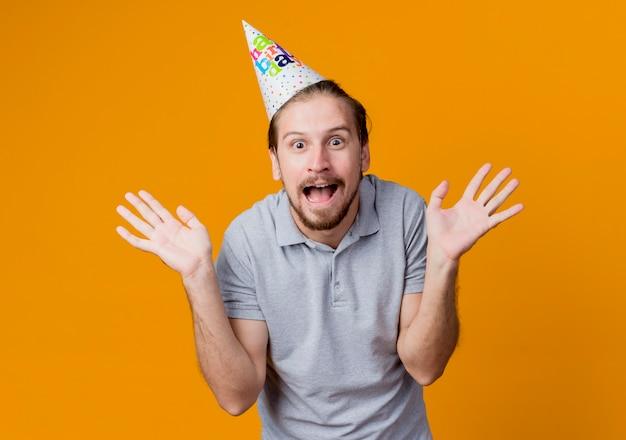 Junger mann in feiertagsmütze überrascht und verwirrt lächelndes geburtstagsfeierkonzept, das über orange wand steht
