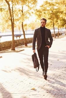 Junger mann in formeller kleidung geht am sonnigen tag im herbstpark spazieren.