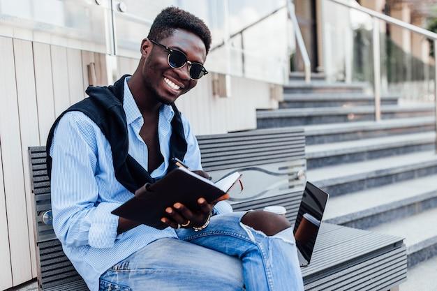 Junger mann in freizeitkleidung, der auf dem stadtplatz sitzt und notiz schreibt. schöne zeit. look des tages.