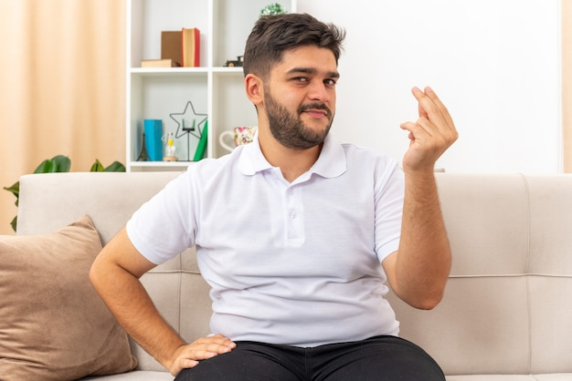 Junger mann in freizeitkleidung, der aussieht, um geld zu verdienen geste reibt finger schlau lächelnd auf einer couch im hellen wohnzimmer sitzend