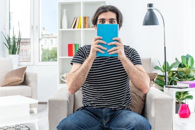 Junger mann in freizeitkleidung, der ein buch vor seinem gesicht hält, glücklich und positiv auf dem stuhl im hellen wohnzimmer sitzend