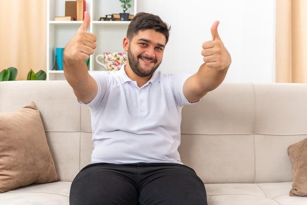 Junger mann in freizeitkleidung, der glücklich aussieht und fröhlich lächelt und daumen nach oben zeigt, sitzt auf einer couch im hellen wohnzimmer sitting