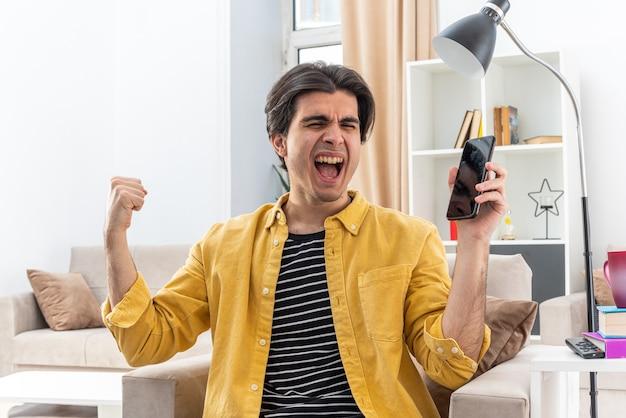 Junger mann in freizeitkleidung, der glücklich und aufgeregt die faust des smartphones hält und sich über seinen erfolg freut, der auf dem stuhl im hellen wohnzimmer sitzt living
