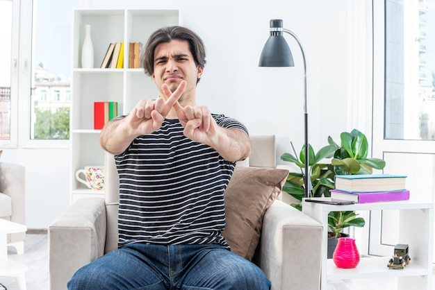Junger mann in freizeitkleidung, der mit stirnrunzelndem gesicht aussieht und verteidigungsgeste macht, die zeigefinger auf dem stuhl im hellen wohnzimmer kreuzt