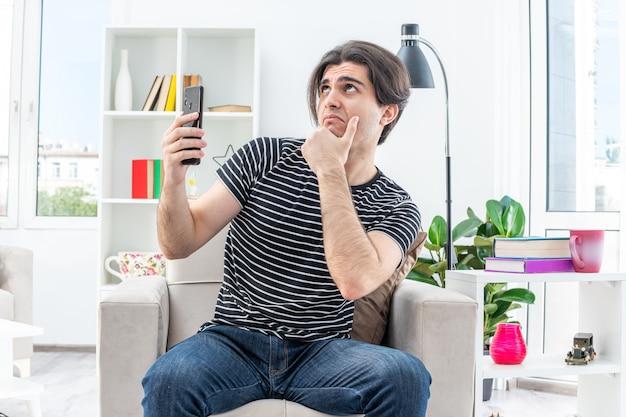 Junger mann in freizeitkleidung, der smartphone hält und mit nachdenklichem gesichtsausdruck aufschaut