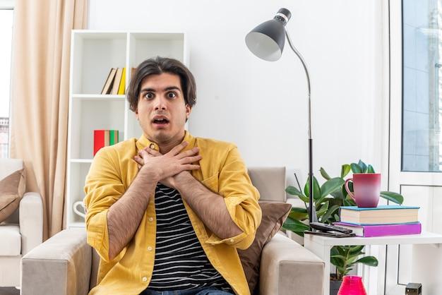 Junger mann in freizeitkleidung, der überrascht aussieht, händchen haltend am hals sitzend auf dem stuhl im hellen wohnzimmer
