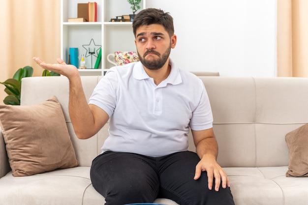 Junger mann in freizeitkleidung, der verwirrt beiseite schaut und etwas mit dem handarm präsentiert, der auf einer couch im hellen wohnzimmer sitzt sitting