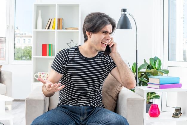 Junger mann in freizeitkleidung, der verwirrt und unzufrieden aussieht, während er auf dem handy im hellen wohnzimmer auf dem stuhl sitzt