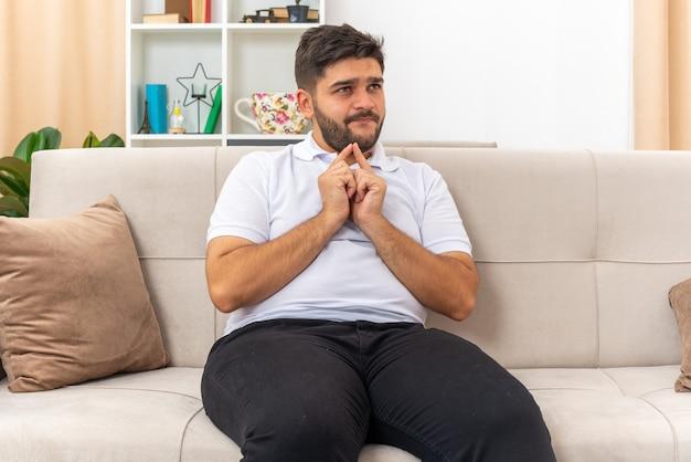 Junger mann in freizeitkleidung, die hände zusammenhält und auf überraschung wartet, die auf einer couch im hellen wohnzimmer sitzt