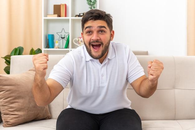 Junger mann in freizeitkleidung glücklich und aufgeregt ballte die fäuste und freute sich über seinen erfolg auf einer couch im hellen wohnzimmer