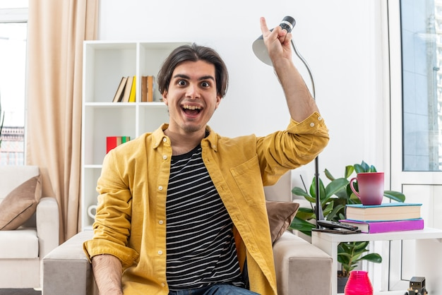Junger mann in freizeitkleidung glücklich und überrascht, der zeigefinger zeigt, der eine neue großartige idee hat, die auf dem stuhl im hellen wohnzimmer sitzt