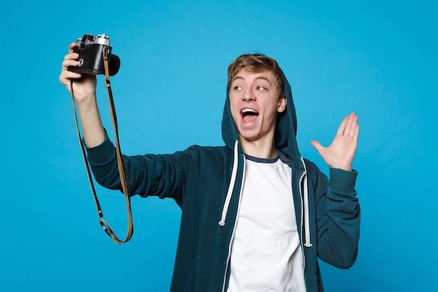 Junger mann in freizeitkleidung macht selfie-aufnahme auf retro-vintage-fotokamera, zeigt palme und verbreitet hand isoliert auf blauer wand menschen aufrichtige emotionen, lifestyle-konzept.
