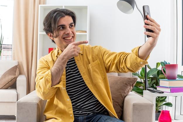 Junger mann in freizeitkleidung macht selfie mit smartphone glücklich und fröhlich und zeigt mit dem zeigefinger auf den bildschirm, der auf dem stuhl im hellen wohnzimmer sitzt