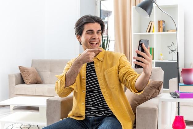 Junger mann in freizeitkleidung mit videoanruf mit smartphone, der mit dem zeigefinger zeigt, glücklich und selbstbewusst auf dem stuhl im hellen wohnzimmer sitzend