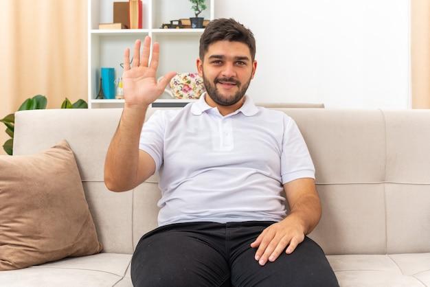 Junger mann in freizeitkleidung sieht glücklich und selbstbewusst aus und winkt mit der hand, die auf einer couch im hellen wohnzimmer sitzt
