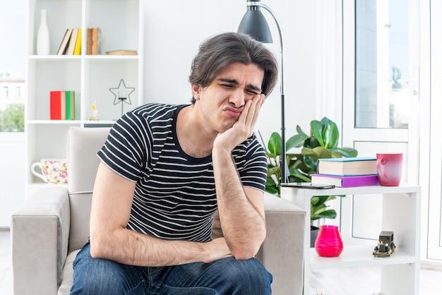 Junger mann in freizeitkleidung sitzt auf dem stuhl mit traurigem gesichtsausdruck und lehnt den kopf auf den arm im hellen wohnzimmer living