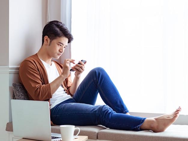Junger mann in freizeitkleidung und mit smartphone