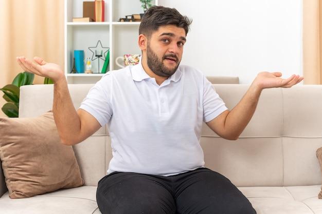 Junger mann in freizeitkleidung verwirrt, die arme zu den seiten ausbreitend, sitzend auf einer couch im hellen wohnzimmer