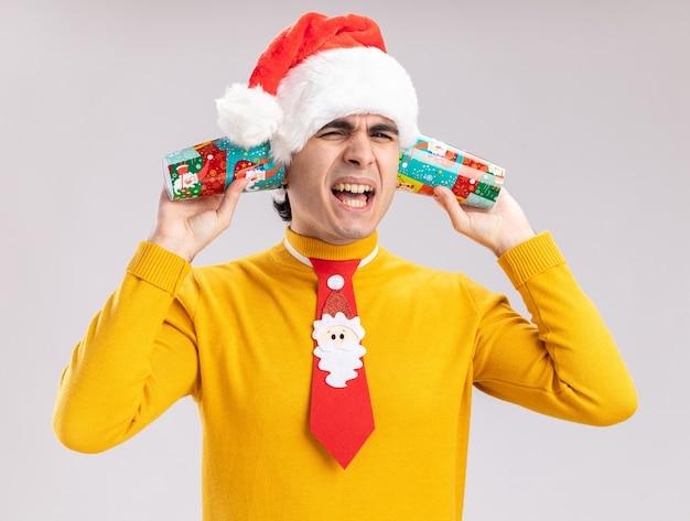 Junger mann in gelbem rollkragenpullover und weihnachtsmütze mit lustiger krawatte, die bunte pappbecher über seinen ohren hält und mit genervtem ausdruck über weißer wand schreit