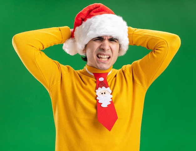 Junger mann in gelbem rollkragenpullover und weihnachtsmütze mit lustiger krawatte, die genervt und gereizt aussieht, mit den händen auf dem kopf, die auf grünem hintergrund stehen