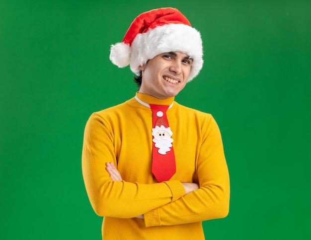 Junger mann in gelbem rollkragenpullover und weihnachtsmütze mit lustiger krawatte, die kamera mit großem lächeln auf gesicht mit verschränkten armen betrachtet, die über grünem hintergrund stehen