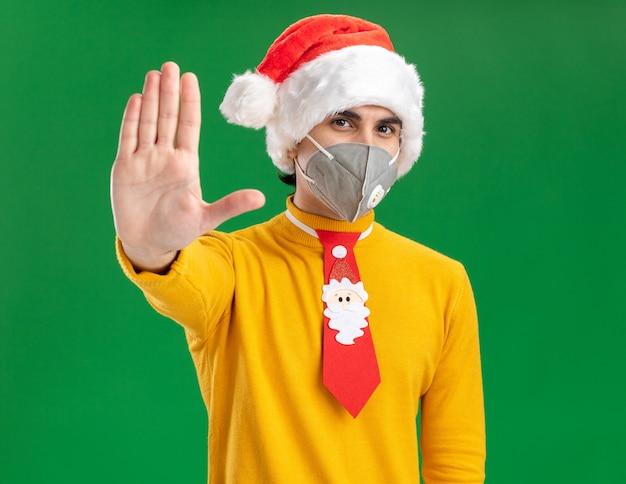 Junger mann in gelbem rollkragenpullover und weihnachtsmütze mit lustiger krawatte mit gesichtsschutzmaske und blick in die kamera mit ernstem gesicht, das eine stoppgeste mit offener hand auf grünem hintergrund macht