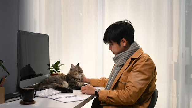 Junger mann in gelber jacke, der online arbeitet und seine katze in einem komfortablen zuhause streichelt.
