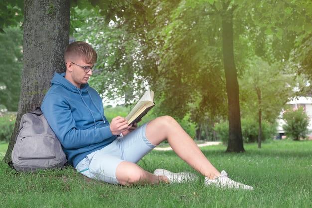 Junger mann in gläsern liest ein buch in einem park, der sich auf baum stützt