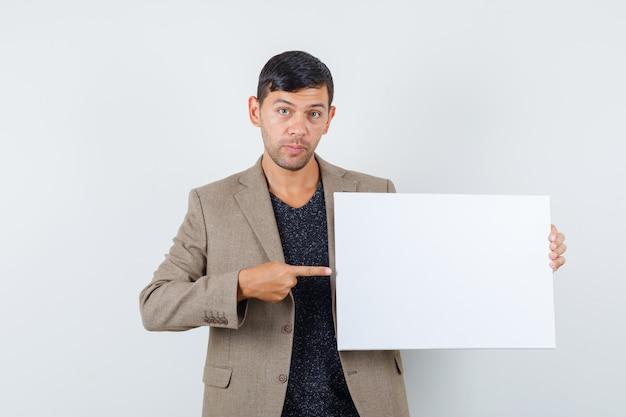 Junger mann in graubrauner jacke, die auf leeres papier zeigt und fokussierte vorderansicht schaut.