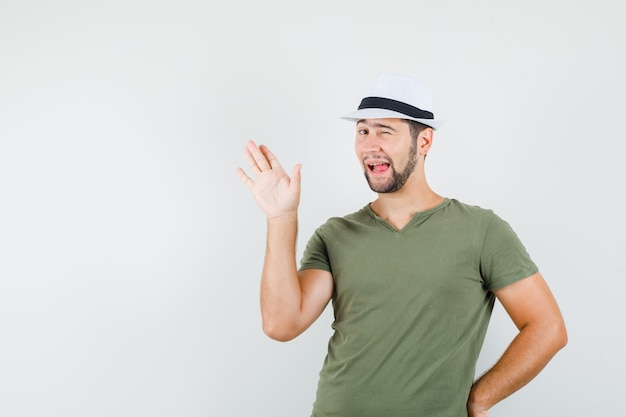 Junger mann in grünem t-shirt und hut, der hand winkt, auge zwinkert, zunge herausstreckt und lustig aussieht