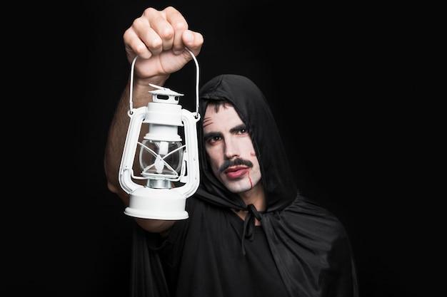 Junger mann in halloween-kostüm, das im studio mit laterne aufwirft