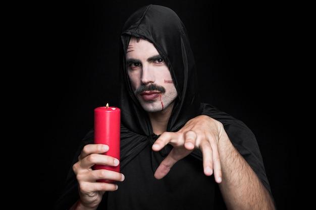 Junger mann in halloween-kostüm, das kerze mit mysteriösem gesicht hält
