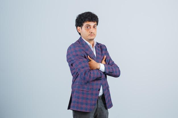 Junger mann in hemd, jacke, hose, die mit verschränkten armen steht und nachdenklich aussieht, vorderansicht.