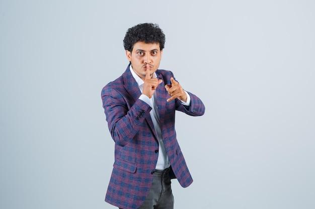 Junger mann in hemd, jacke, hose, die stille zeigt, auf die kamera zeigt und selbstbewusst aussieht, vorderansicht.
