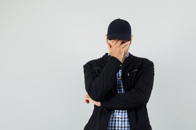 Junger mann in hemd, jacke, mütze, die hand auf gesicht hält und verärgert schaut
