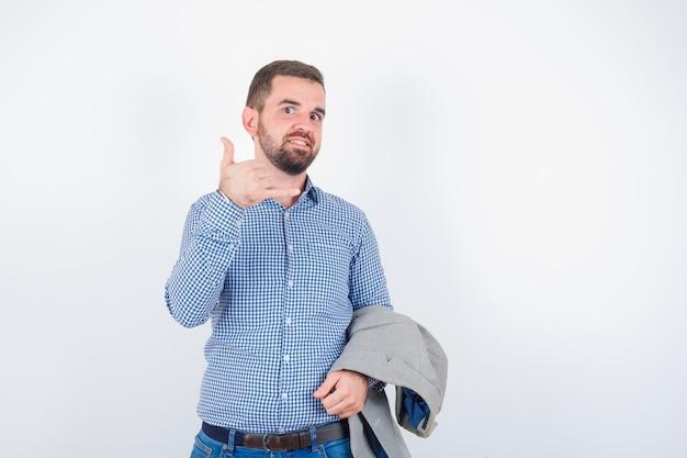 Junger mann in hemd, jeans, anzugjacke, die anzugjacke hält, während telefongeste zeigt und glücklich, vorderansicht schaut.
