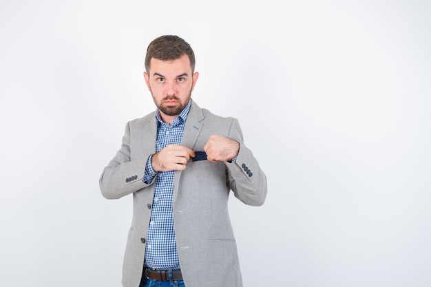 Junger mann in hemd, jeans, anzugjacke, die taschentuch der tasche hält und selbstbewusst aussieht, vorderansicht.