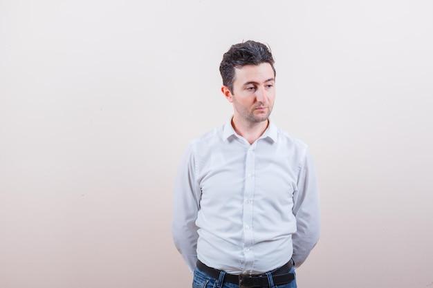 Junger mann in hemd, jeans, der wegschaut, die hände hinter dem rücken hält und besorgt aussieht