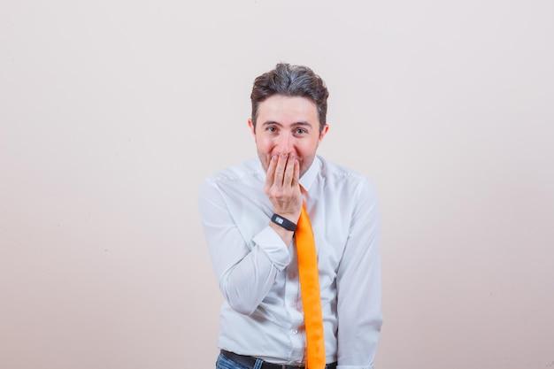 Junger mann in hemd, krawatte, jeans, der hand auf den mund hält und erstaunt aussieht