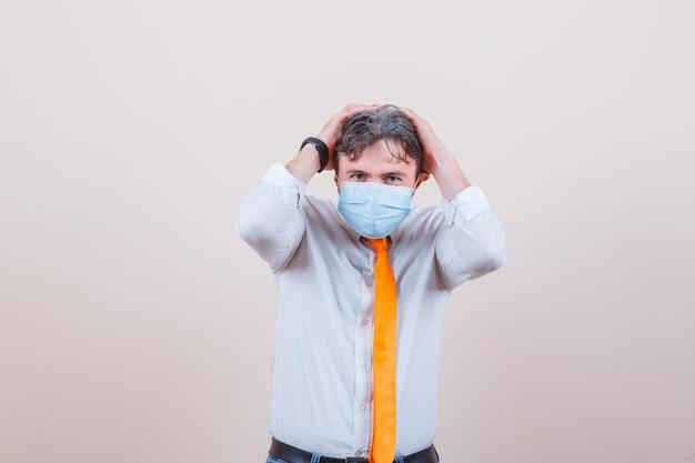 Junger mann in hemd, krawatte, maske, die den kopf in die hände hält und ängstlich aussieht